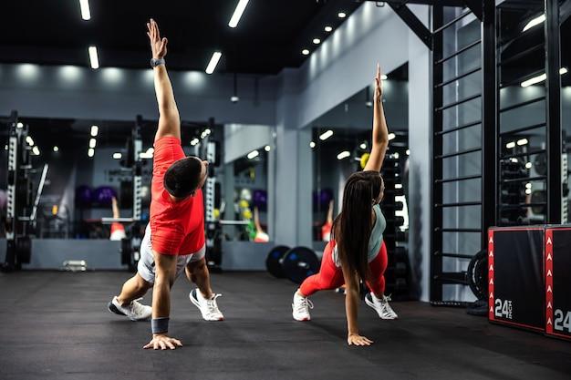 男性と女性は腕を上げて板の位置にあり、全身と体の安定のために運動をしています。
