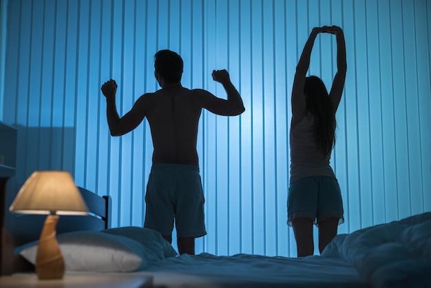 Мужчина и женщина делают упражнения в спальне. ночное время