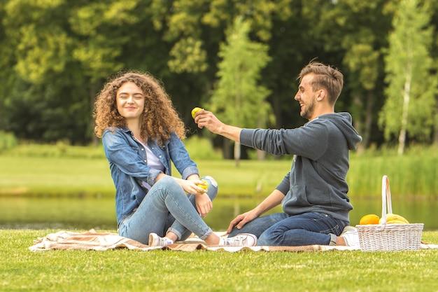 男と女はピクニックでリンゴを食べる