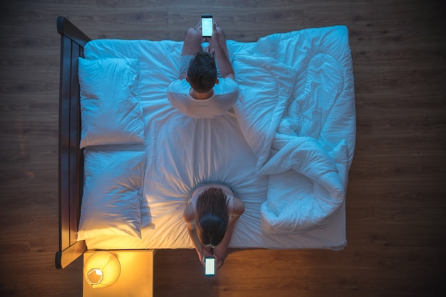 Мужчина и женщина держат телефон на кровати. вечер ночное время. вид сверху