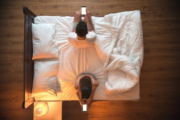 Мужчина и женщина держат телефон на кровати. вид сверху