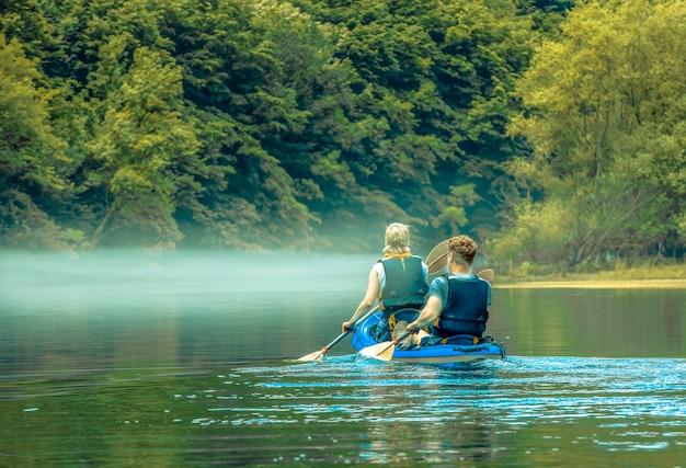 산 호수에 안개에 카약에 남자와 여자