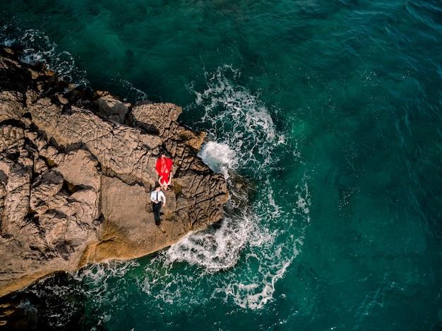 빨간 드레스를 입은 남자와 여자는 바위 해안에 나란히 누워 서로를 바라본다.