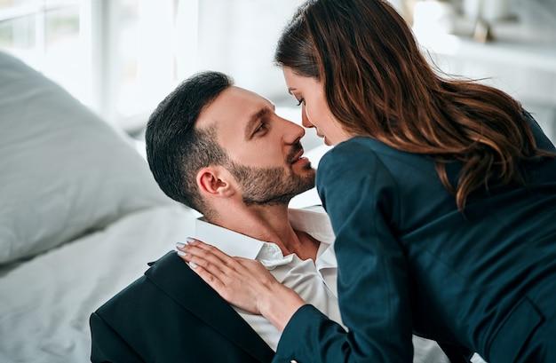 ベッドでキスするスーツを着た男女