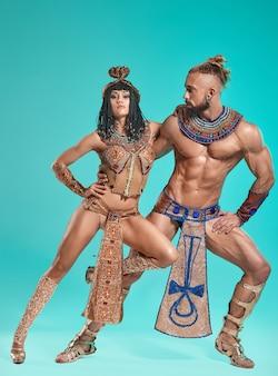 青いスタジオの背景にエジプトのファラオとクレオパトラの画像の男と女