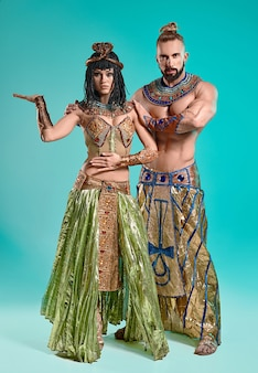 파란색 스튜디오 배경에 이집트 파라오와 클레오파트라의 이미지에 있는 남자와 여자
