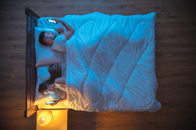 Мужчина и женщина звонят на кровати. вечер ночное время. вид сверху
