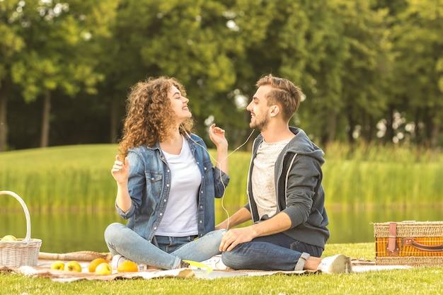 男と女は公園でイヤホンを持って座っています