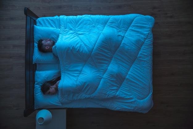 Мужчина и женщина спят в постели. ночное время. вид сверху