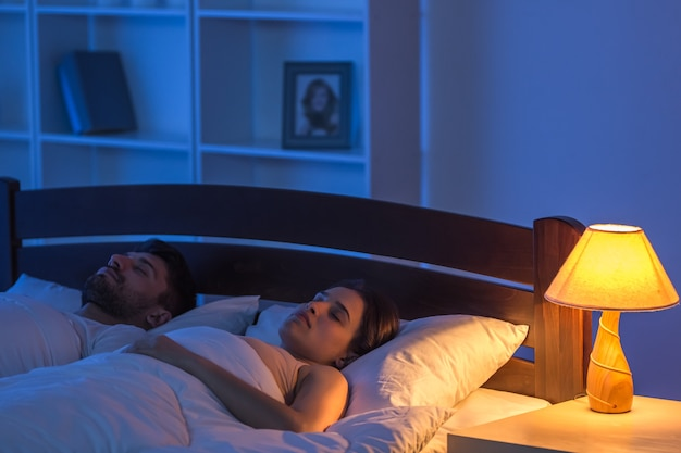 Мужчина и женщина спят в спальне. ночное время