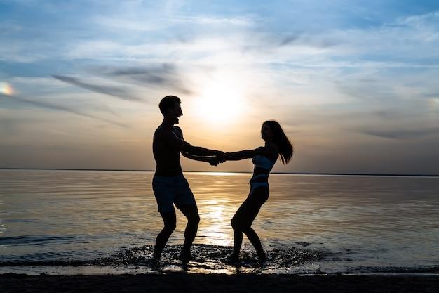 美しい夕日を背景に水中で回転する男と女