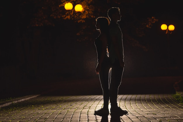 Мужчина и женщина стоят на темной улице. ночное время