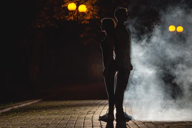 Мужчина и женщина стоят на темной улице на фоне дыма. ночное время