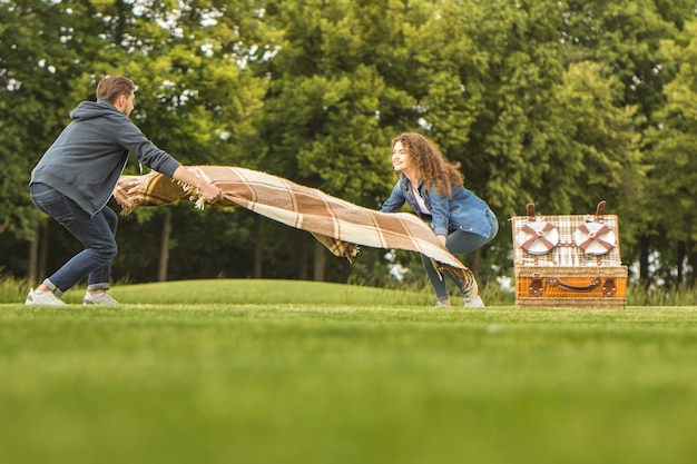 男と女は公園でカバーを持って立っています