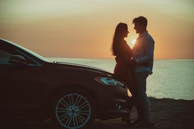 아름다운 바다 해안을 배경으로 차 근처에 서 있는 남자와 여자
