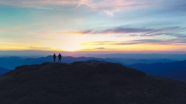 夕日を背景に山に立っている男女