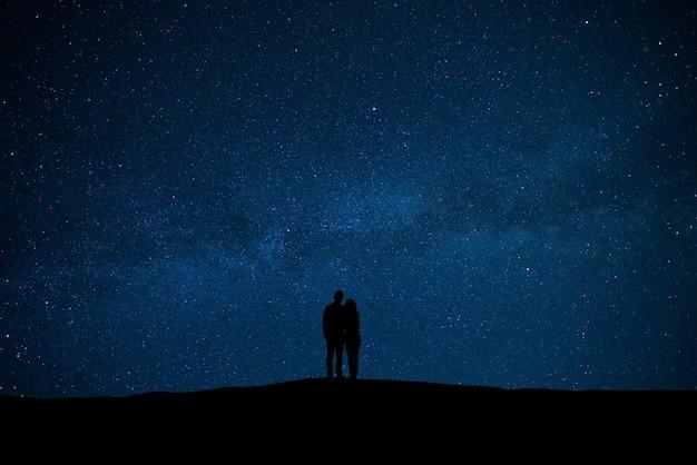 별 배경으로 하늘에 서 있는 남자와 여자