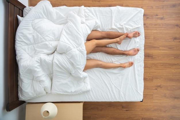 ベッドに横たわっている毛布の下の男と女。上からの眺め