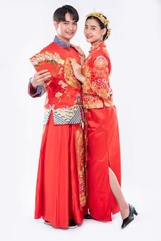 치파오를 입은 남녀가 전통의 날에 선물 금과 현금을 보여줍니다.