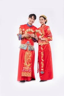 男性と女性は伝統的な日に家族への赤い贈り物のお金を準備してチャイナドレスを着ています