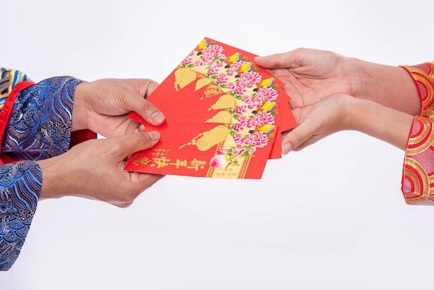 男と女は家族を送るために赤い贈り物のお金でチャイナドレスを着ています