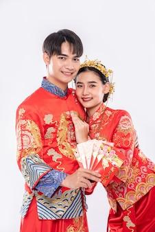男性と女性は伝統的な日に家族からの赤い贈り物のお金を見せてチャイナドレスを着ています