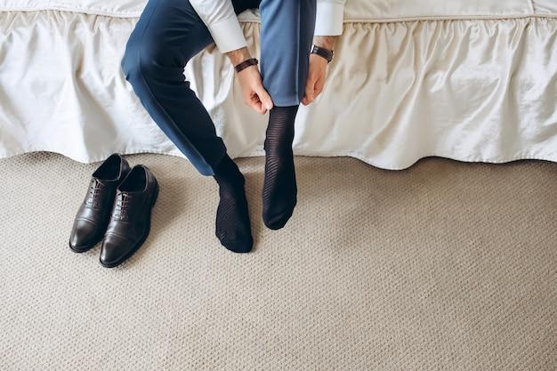 Мужчина устраивает носки перед тем, как надеть ботинки