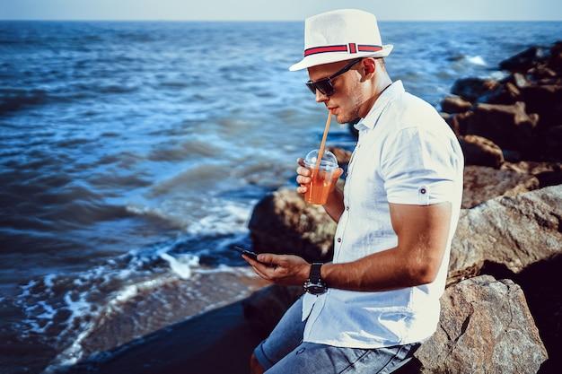 Человек на курорте в белой рубашке и шляпе сидит на скале на море.