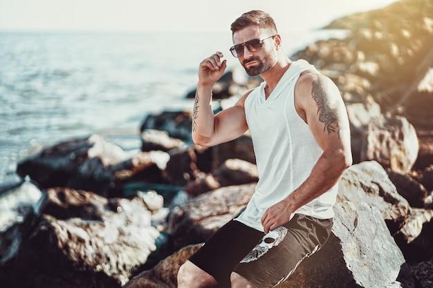 Мужчина на курорте в белой рубашке и солнцезащитных очках сидит на скале у моря