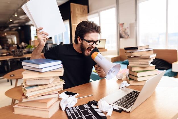 Мужчина за столом кричит на ноутбук с мегафоном.