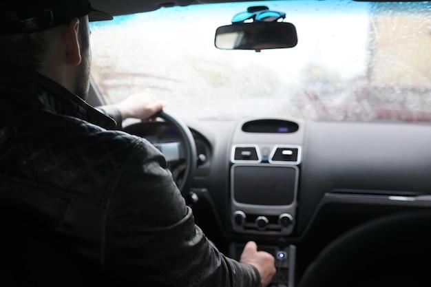Человек за рулем автомобиля во время вождения в дождливый день