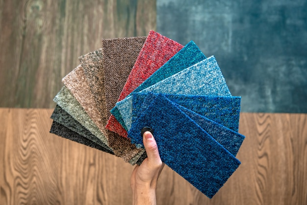 Мужчина выбирает цвет нового ковра по шаблону книги в магазине напольных покрытий
