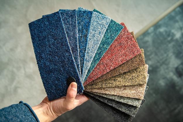 男はフローリングショップのパターンブックに従って新しいカーペットの色を選択します