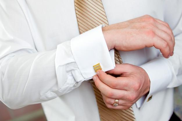 남자는 셔츠에 커프스 단추를 걸쇠