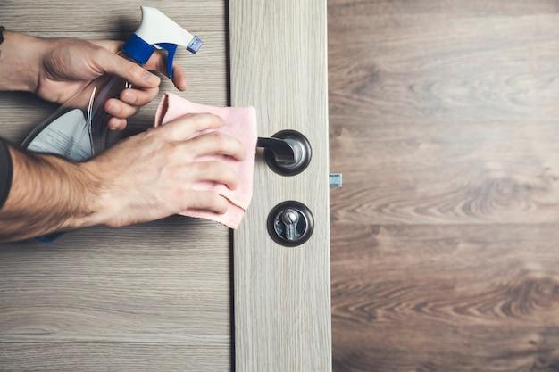 Мужчина моет дверь жидкостью.