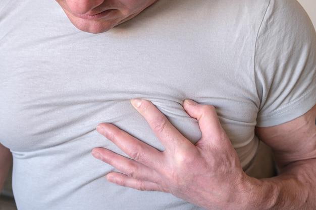 Мужчина схватился за грудь. стенокардия сердечного приступа на белом