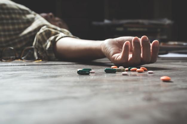 薬を過剰摂取して自殺する男。過量の丸薬のクローズアップ