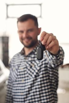 남자는 새로운 자동차 모델 범위를 고려하고 자신에게 가장 적합한 것을 선택하려고합니다.