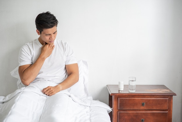 男は咳をして口に手をかざし、ベッドに座りました。