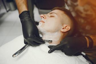 The man cuts his beard in the barbershop