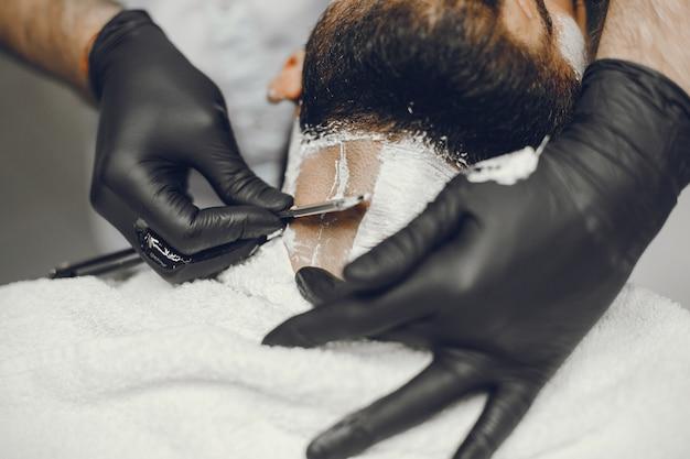Человек режет бороду в парикмахерской.