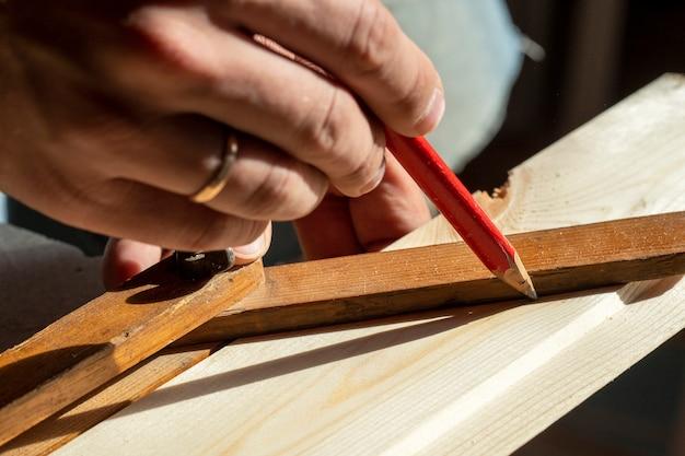 남자는 원하는 각도를 측정하는 건설 보드에 연필로 선을 그립니다