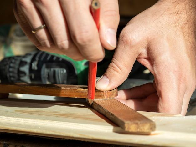 Мужчина рисует карандашом линию на строительной доске, измеряя нужный угол.