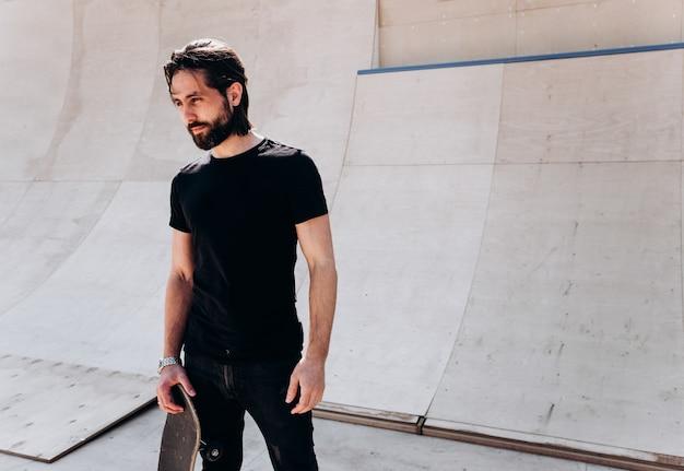 스케이트보드를 손에 들고 있는 세련된 캐주얼 옷을 입은 남자는 화창한 날 미끄럼틀 옆에 있는 스케이트 공원에 서 있습니다.