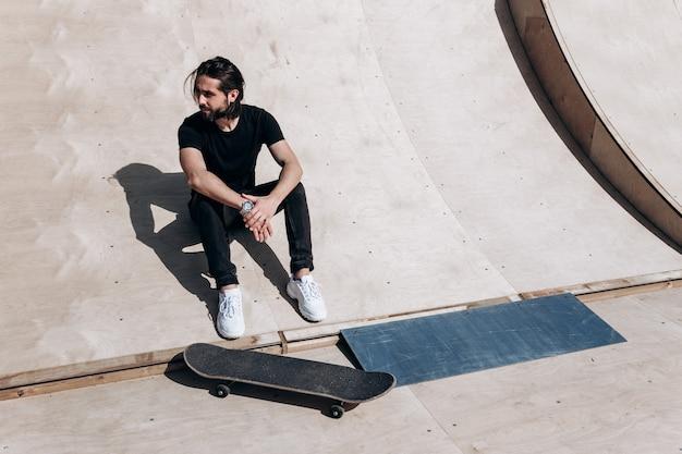 세련된 캐주얼 옷을 입은 남자가 화창한 날 스케이트장에 있는 스케이트보드 옆 미끄럼틀에 앉아 있다.