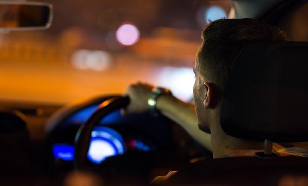 남자는 밤 도시에서 차를 운전합니다. 좌측 교통