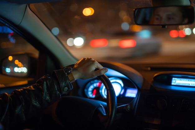 男は道路で車を運転します。夕方の夜