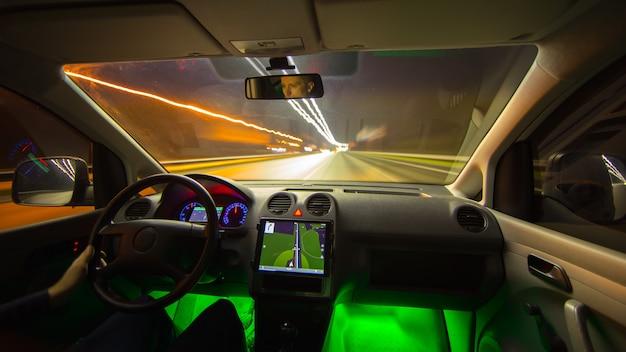 Мужчина водит машину с gps в ночном городе. широкий угол. вид изнутри