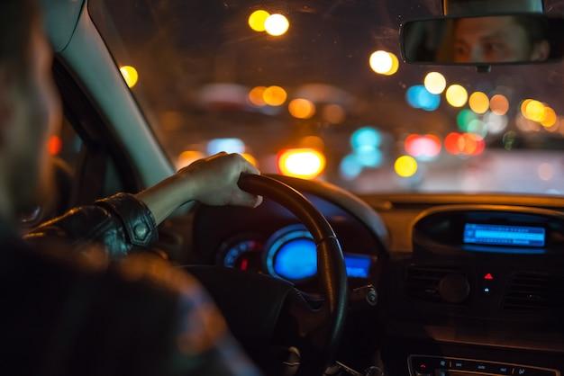 男は街で現代の車を運転します。夕方の夜