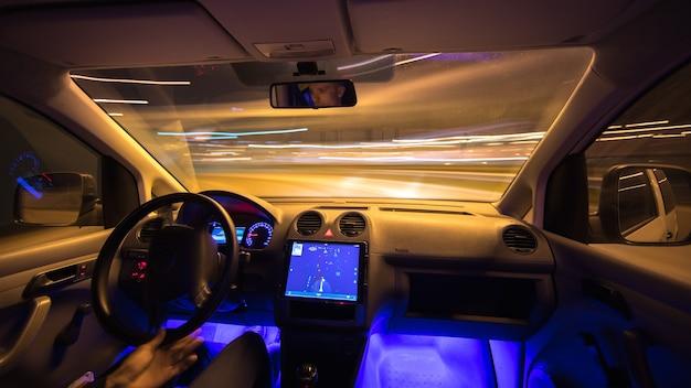 남자는 탐색과 함께 도시 도로에서 운전합니다. 저녁 밤 시간